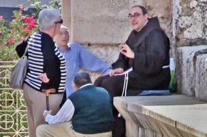 A Franciscan brother talks to pilgrims in Capernaum's Synagogue.